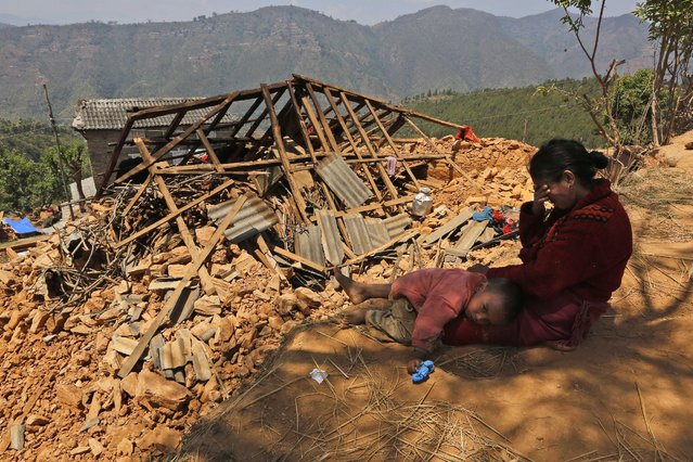 A Nepalese woman sits with her son near their house, destroyed in last week's earthquake, in Pauwathok village, Sindhupalchok district, Nepal, Saturday, May 2, 2015. Life has been slowly returning to normal in Kathmandu, but to the east, angry villagers in parts of the Sindhupalchok district said Saturday they were still waiting for aid to reach them. (Photo by Manish Swarup/AP Photo)
