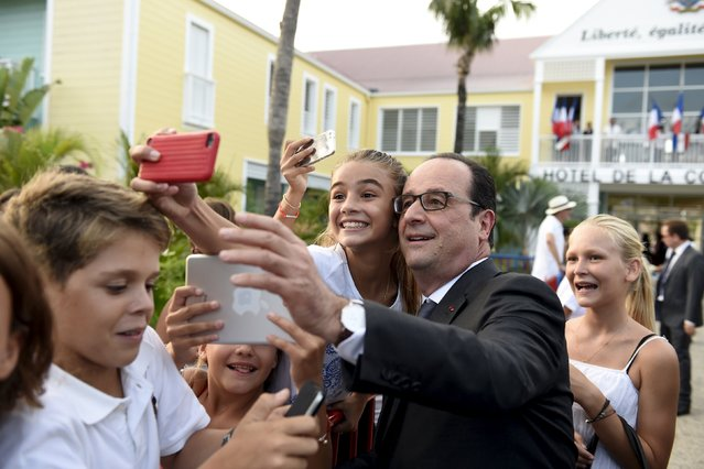 France's President Francois Hollande takes a picture with students in Saint Barthelemy on May 8, 2015, as part of a five days visit to the Caribbean including Guadeloupe, Martinique, Cuba and Haiti. (Photo by Alain Jocard/AFP Photo)