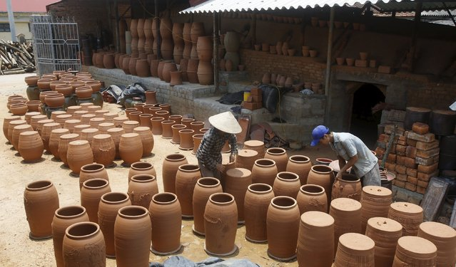 Workers dry products at a factory producing clay pots at Phu Lang pottery village in Bac Ninh province, Vietnam, May 14, 2015. (Photo by Reuters/Kham)