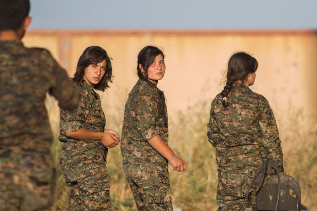 Female Kurdish People's Protection Units (YPG) fighters walk at silos of Aliya village after saying that they retook control of the area from Islamic State in the southern countryside of Ras al-Ain May 13, 2015. (Photo by Rodi Said/Reuters)