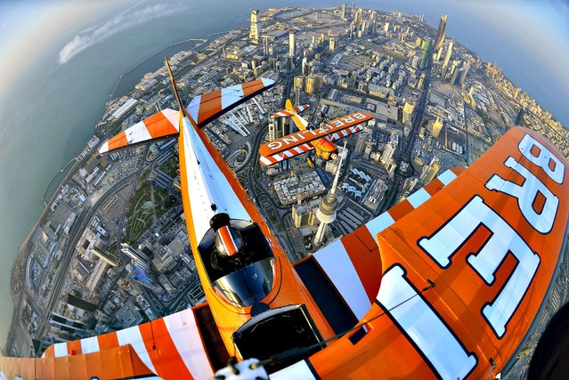 Breitling Wingwalker Freya Paterson, from Liverpool, UK, flies above Kuwait City's iconic Water Towers with pilots David Barrell and Martyn Carrington on Thursday, March  6, 2014. The team loop and roll up to 160 mph enduring G-forces of 4-5g. Crowds are expected to line the Kuwaiti coastline to catch a glimpse of the Wingwalking team on Saturday, March 8, 2014, to mark the opening of the first dedicated boutique in the city for the prestigious watch brand. (Photo by Katsuhiko Tokunaga/Breitling via AP Images)
