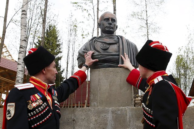 Cossacks stand next to a bust of Russian President Vladimir Putin which depicts him as a Roman emperor, during its unveiling ceremony in Leningrad region, Russia, May 16, 2015. (Photo by Maxim Zmeyev/Reuters)