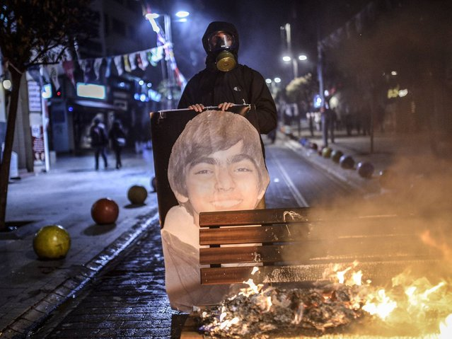 A protester holds a picture of Berkin Elvan during clashes with riot police in Istanbul. (Photo by Bulent Kilic/AFP Photo)