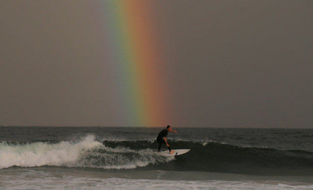 A surfer rides a wave under a rainbow appearing off the coast of Sydney's Wanda Beach in Australia, February 25, 2017 as the setting sun illuminates a passing rain shower. (Photo by Jason Reed/Reuters)
