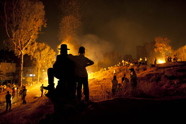 Ultra-Orthodox Jews stand next to bonfires during Lag Ba'Omer celebrations to commemorate the end of a plague said to have decimated Jews in Roman times, in Bnei Brak, Israel, Wednesday, May 9, 2012. (Photo by Oded Balilty/AP Photo)