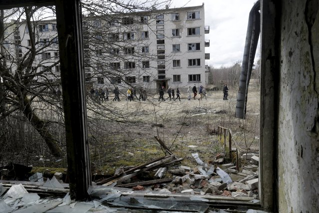 People walk past an abandoned apartment house in the ghost town of a former Soviet military radar station near Skrunda, Latvia, April 9, 2016. (Photo by Ints Kalnins/Reuters)