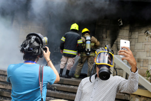 A journalist takes a selfie as firefighters extinguish burning tires, set alight at the entrance of the U.S. embassy by demonstrators during a protest against President Juan Orlando Hernandez government's plans to privatise healthcare and education, in Tegucigalpa, Honduras on May 31, 2019. (Photo by Jorge Cabrera/Reuters)