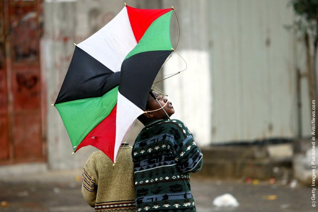 A Palestinian boy looks back as the wind turns his umbrella, made up of the Palestinian national flag colors