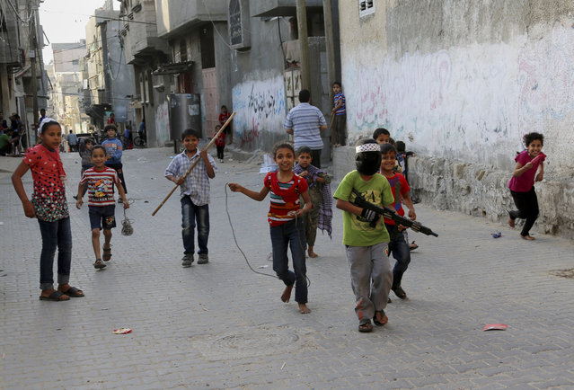 Palestinian children play at the main road in Jebaliya refugee camp in the northern Gaza Strip, Thursday, May 14, 2015. (Photo by Adel Hana/AP Photo)