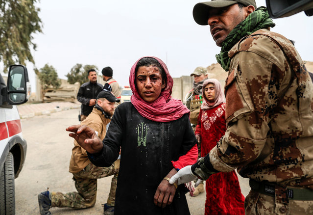 A woman injured in a mortar attack walks toward a ambulance after she was treated by medics in a field clinic as Iraqi forces battle with Islamic State militants, in western Mosul, Iraq March 2, 2017. (Photo by Zohra Bensemra/Reuters)