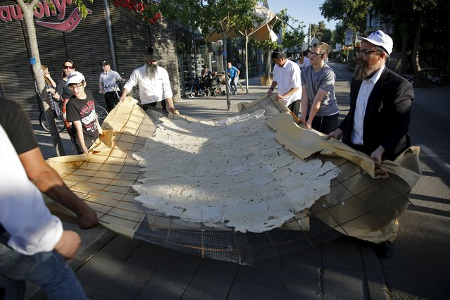 Israeli ultra-Orthodox men carry what they claim is the world's largest matza which they baked  in Jerusalem, April 17, 2016. (Photo by Ronen Zvulun/Reuters)