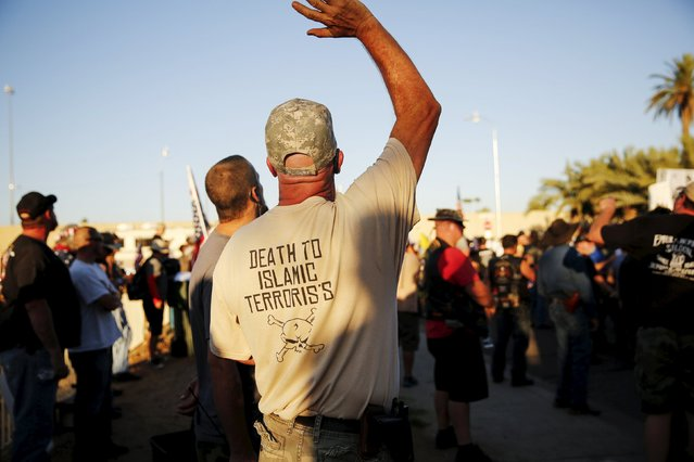 """A demonstrator waves during the """"Freedom of Speech Rally Round II"""" across from the Islamic Community Center in Phoenix, Arizona May 29, 2015. More than 200 protesters, some armed, berated Islam and its Prophet Mohammed outside an Arizona mosque on Friday in a provocative protest that was denounced by counterprotesters shouting """"Go home, Nazis,"""" weeks after an anti-Muslim event in Texas came under attack by two gunmen.  REUTERS/Nancy Wiechec"""