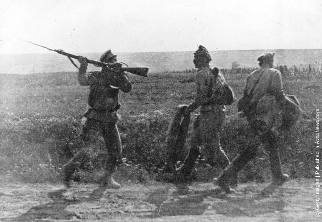 Two army deserters are threatened by a Russian soldier with raised rifle and bayonet, 1914