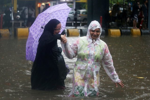 Women wade through a waterlogged street during heavy rains in Mumbai, June 28, 2019. (Photo by Francis Mascarenhas/Reuters)
