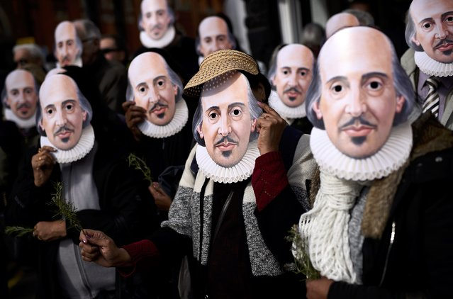 People hold up face masks with William Shakespeare's portrait during celebrations to mark the 400th anniversary of the playwright's death in the city of his birth, Stratford-Upon-Avon, Britain, April 23, 2016. (Photo by Dylan Martinez/Reuters)