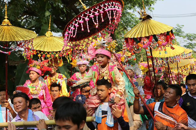 Tai Yai boys are carried in a procession by their relatives during the Poy Sang Long Festival on April 7, 2014 in Mae Hong Son, Thailand. Poy Sang Long is a Buddhist novice ordination ceremony of the Shan people or Tai Yai, an ethnic group of Shan State in Myanmar and northern Thailand. Young boys aged between 7 and 14 are ordained as novices to learn the Buddhist doctrines. It's believed that they will gain merit for their parents by ordaining. (Photo by Taylor Weidman/Getty Images)