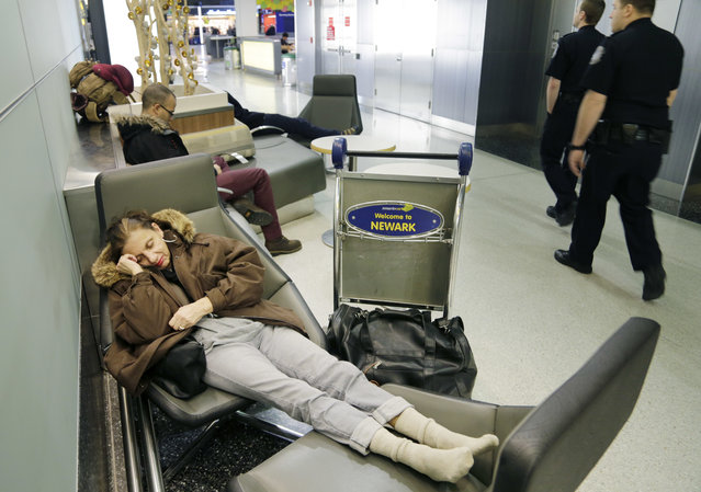 Yvonne Mouskourie, of Tom's River, N.J., makes herself comfortable after her morning flight to Florida was canceled at Newark Liberty International Airport in Newark, N.J., Tuesday, March 14, 2017. A storm pounded the Northeast with more than a foot of snow in places Tuesday, paralyzing much of the Washington-to-Boston corridor after a remarkably mild February had lulled people into thinking the worst of winter was over. (Photo by Seth Wenig/AP Photo)