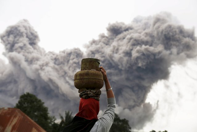 A resident carries a gas canister as an ash cloud hovers above during an eruption of Mount Sinabung volcano at Tiga Serangkai village in Karo Regency, North Sumatra province, Indonesia June 24, 2015. More than 10,000 people from 12 villages, who are living around the slopes of Mount Sinabung, left their homes and moved to refugee camps, local media reported. (Photo by Reuters/Beawiharta)
