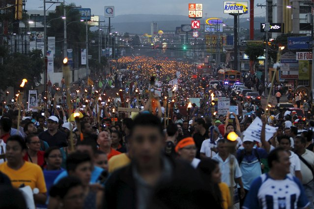 People take part in a march to demand the resignation of Honduras' President Juan Hernandez in Tegucigalpa June 26, 2015. Thousands of angry, torch-bearing Hondurans marched on Friday to call for the resignation of Hernandez and demand an independent probe into one of the worst corruption scandals in the country's history. (Photo by Jorge Cabrera/Reuters)