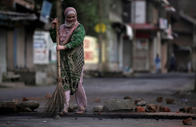 A woman removes pieces of stones and bricks from a road during restrictions after the government scrapped special status for Kashmir, in Srinagar August 7, 2019. (Photo by Danish Ismail/Reuters)