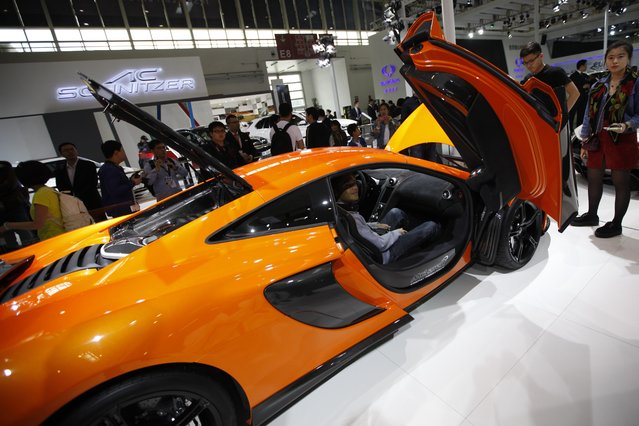 """A visitor (C) poses for a photo in a Mclaren car on display at the China International Exhibition Center new venue during the """"Auto China 2014"""" Beijing International Automotive Exhibition in Beijing on April 20, 2014. Leading automakers are gathering in Beijing for the kickoff of China's biggest car show, but lackluster growth and environmental restrictions in the world's largest car market have thrown uncertainty into the mix. (Photo by AFP Photo)"""