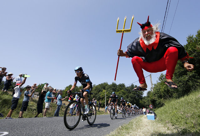 """Didi Senft, a cycling enthusiast better known as """"El Diablo"""" (The Devil), jumps as the pack of riders cycles during the twelfth 218km stage of the centenary Tour de France cycling race from Fougeres to Tours July 11, 2013. (Photo by Eric Gaillard/Reuters)"""