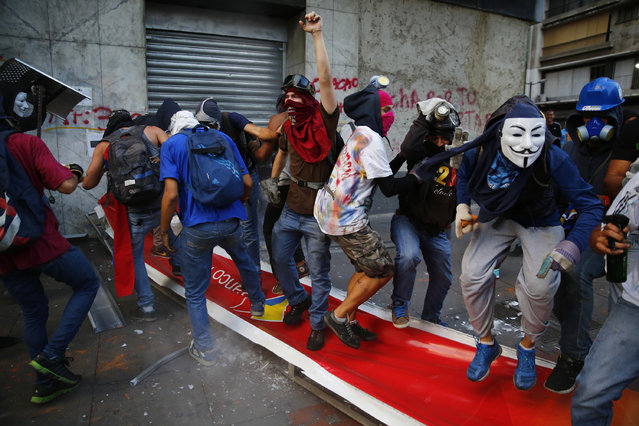 "Anti-government protesters jump and step on a banner of Banco de Venezuela after bringing down the banner during riots in Caracas April 20, 2014. Masked youths battled police, protesters burned and hung from lamp-posts effigies of President Nicolas Maduro and marchers demanded the ""resurrection"" of democracy on a volatile Easter Sunday in Venezuela. (Photo by Jorge Silva/Reuters)"
