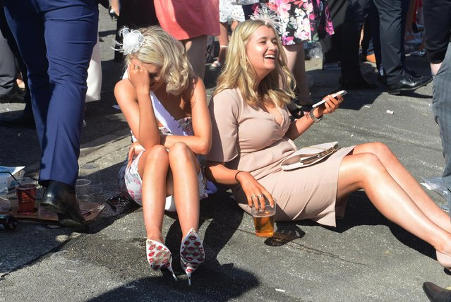 These women get the giggles as they take a break with a pint in the sunshine during the Grand National Festival at Aintree Racecourse on April 7, 2017 in Liverpool, England. (Photo by South West News Service)