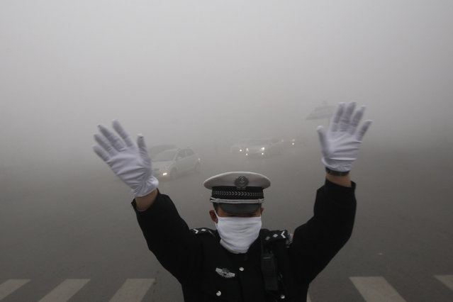 A traffic policeman signals to drivers during a smoggy day in Harbin, Heilongjiang province, October 21, 2013. The second day of heavy smog with a PM 2.5 index has forced the closure of schools and highways, exceeding 500 micrograms per cubic meter on Monday morning in downtown Harbin, according to Xinhua News Agency. (Photo by Reuters/China Daily)