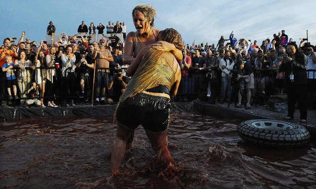 Participants wrestle in barbecue sauce at Talladega Superspeedway in Talladega, Alabama on May 2, 2014, where the Sprint Cup Aaron's 499 auto race starts Sunday. (Photo by Rainier Ehrhardt/Associated Press)
