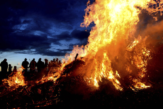 In this April 15, 2017 photo spectators watch the traditional Easter bonfire in Wartjenstedt, Germany. (Photo by Maurizio Gambarini/DPA via AP Photo)