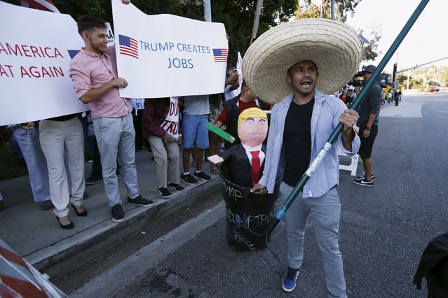 A Trump protester carries a pinata of Trump in a trash can past Trump supporters outside the Luxe Hotel, where Republican presidential candidate Donald Trump was expected to speak in Brentwood, Los Angeles, California, United States July 10, 2015. (Photo by Lucy Nicholson/Reuters)