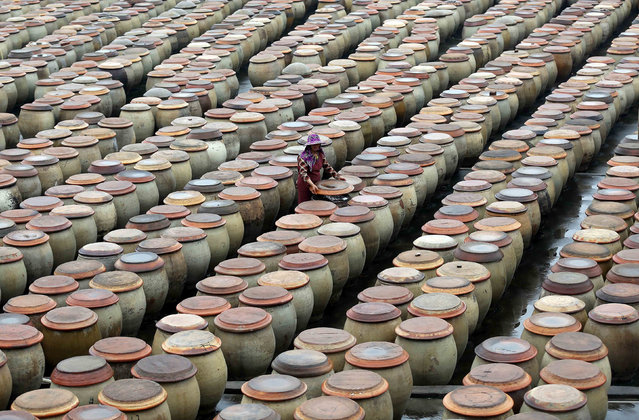 A woman works at a factory using traditional method to produce soy sauce in Jinjiang, Fujian Province, China, April 25, 2016. (Photo by Reuters/China Daily)