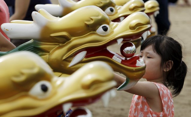 A girl looks at boat decorations during the Chinese dragon boat festival in the outskirts of Panama City, July 12, 2015. (Photo by Carlos Jasso/Reuters)
