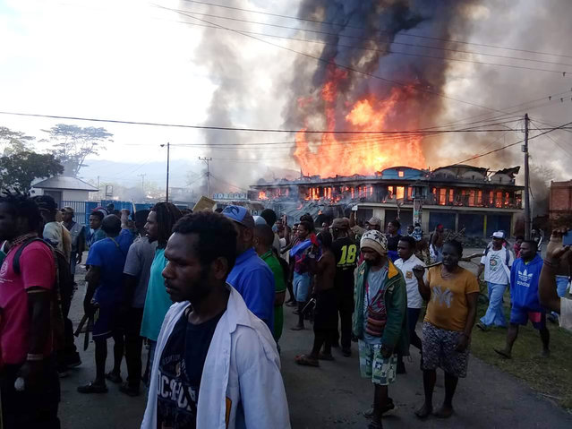 People gather as shops burn in the background during a protest in Wamena in Papua province, Indonesia, Monday, September 23, 2019. Hundreds of protesters in Indonesia's restive Papua province set fire to homes and other buildings Monday in a protest sparked by rumors that a teacher had insulted students, and a soldier was killed in another protest in the region, police said. (Photo by AP Photo/Stringer)