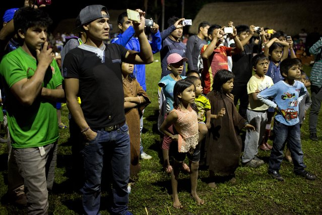 In this June 23, 2015 photo, Ashaninka Indians make pictures with their cell phones as they watch local beauty contestants compete, in Otari Nativo, Pichari, Peru. It was the fifth beauty contest held among the annual festivities marking the founding of the Ashaninka community of Otari Nativo, which is located in a valley near the Apurimac, Ene and Mantaro rivers in the world's largest coca growing region. (Photo by Rodrigo Abd/AP Photo)