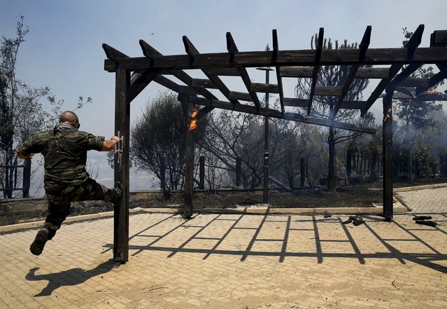 A military man kicks a wooden structure of fire at a children's play ground in an Athens neighborhood during a forest fire, July 17, 2015. (Photo by Yannis Behrakis/Reuters)