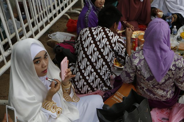 A Muslim woman applies lipstick after the Eid al-Fitr prayers marking the end of the Muslim holy month of Ramadan in Hong Kong, Saturday, July 18, 2015. (Photo by Kin Cheung/AP Photo)