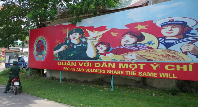 A soldier stands parks his motorcycle in front of a banner at the headquarters of the Division 308 special military force in Xuan Mai town, outside Hanoi July 10, 2015. (Photo by Greg Torode/Reuters)