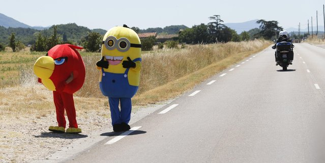 Two disguised spectators wait for the riders to pass during the sixteenth stage of the Tour de France cycling race over 201 kilometers (124.9 miles) with start in Bourg-de-Peage and finish in Gap, France, Monday, July 20, 2015. (Photo by Christophe Ena/AP Photo)