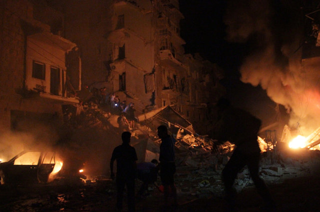 Emergency teams extinguish flames following a reported barrel-bomb attack on the northern Syrian city of Aleppo on May 26, 2014. (Karam Al-Masri/AFP/Getty Images)