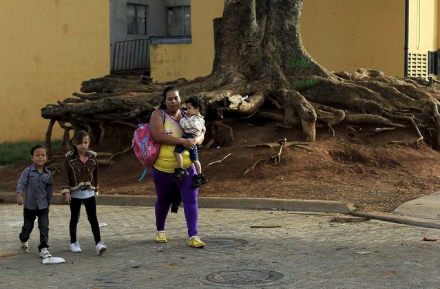 Hazel Castillo walks with her children to an aerobics class in Los Guidos de Desamparados July 23, 2015. (Photo by Juan Carlos Ulate/Reuters)