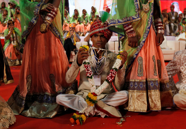A physically challenged groom holds a garland during a mass wedding ceremony organised for underprivileged and physically challenged couples in Mumbai, India, May 29, 2016. (Photo by Danish Siddiqui/Reuters)