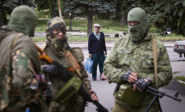 A man looks at armed pro-Russian separatists at a town center in Snizhnye in eastern Ukraine June 12, 2014. (Photo by Shamil Zhumatov/Reuters)
