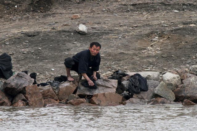 A North Korean washes clothes on the banks of the Yalu River, near the North Korean town of Sinuiju, opposite the Chinese border city of Dandong, April 5, 2015. (Photo by Jacky Chen/Reuters)