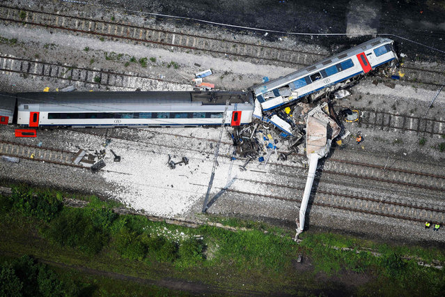 This aerial picture taken on June 6, 2016, shows the scene of a collision between a freight train and a passengers train on their way between Liege and Namur, in Saint-Georges-sur-Meuse, Eastern Belgium. Investigators worked through the wreckage of a high speed train crash in eastern Belgium on Monday that killed at least three people and injured nine others. A fast-moving passenger train late Sunday slammed violently into the back of a slow-moving freight train that was travelling on the same track for reasons that remain unexplained. (Photo by Laurie Dieffembacq/AFP Photo)