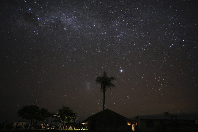 In this May 17, 2017 photo, the Milky Way lights up the sky above a ranch where cowboys spend the night during a round up, in Corumba,  in the Pantanal wetlands of Mato Grosso do Sul state, Brazil. Ranchers here contract out the grazing business, and being a cowboy is reasonably well-paying for the region. (Photo by Eraldo Peres/AP Photo)