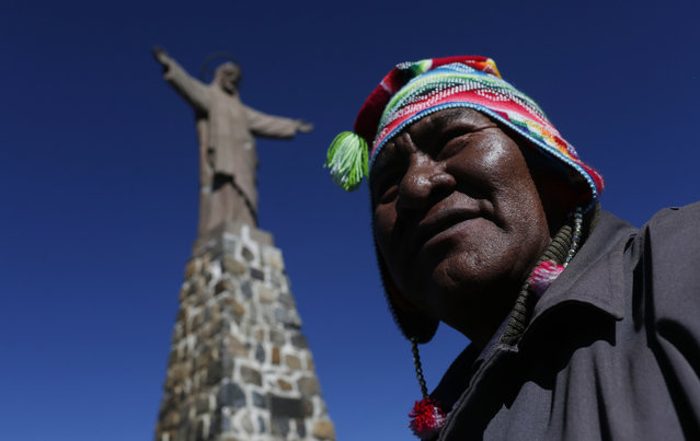 "An Aymara priest leads a prayer after an offering ceremony to ""Pachamama"", or Mother Earth, on La Cumbre, a mountain that is considered scared ground, on the outskirts of La Paz, Bolivia, Saturday, August 1, 2015. (Photo by Juan Karita/AP Photo)"