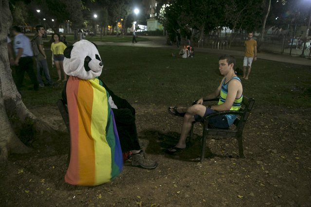 A man dressed in a panda costume sits covered by the gay pride flag during a protest against the violence towards the gay community in Tel Aviv August 1, 2015. Thousands of Israelis came to show solidarity after an ultra-Orthodox Jewish man stabbed and wounded six participants, two of them seriously, in the annual Gay Pride parade in Jerusalem on Thursday, with police saying the suspect was jailed for a similar attack 10 years ago. (Photo by Baz Ratner/Reuters)