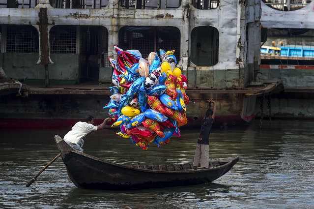 A man holds balloons as he crosses the Buriganga river on a boat in Dhaka, Bangladesh on October 18, 2019. (Photo by Munir Uz Zaman/AFP Photo)
